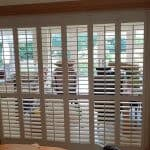 Plantation shutter installed between kitchen and dining room.